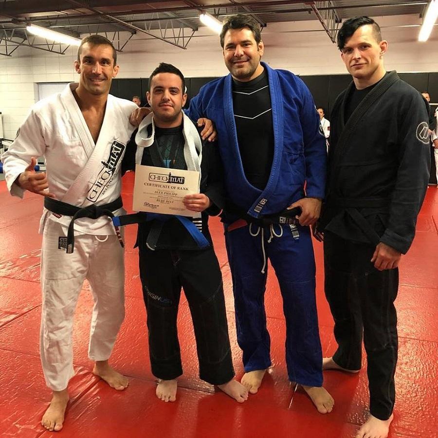 Three Brazilian jiu jitsu black belts with newly promoted blue belt